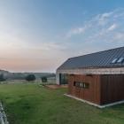 Maison Des Volumes simples et des matériaux naturels, définissant la maison dans le paysage par Kropka Studio
